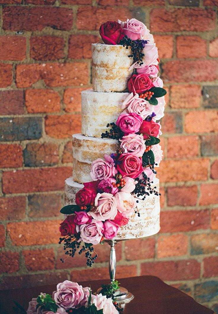 Tall naked (w/o frosting) wedding cake with roses cascading from the top to the bottom.