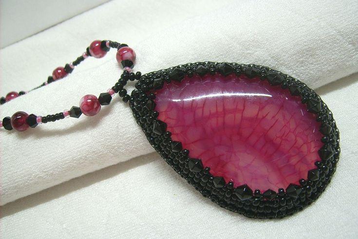 Ny-561. Pink színű, achát ásvány, és fekete üveg gyöngyös medálos nyaklánc. A nyaklánc hossza: 51 cm. A medál mérete: 65 x 42 mm. Ára: 1400.-Ft.
