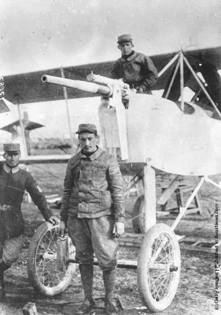 Greek airmen stand with a Voisin plane, armed with a cannon.