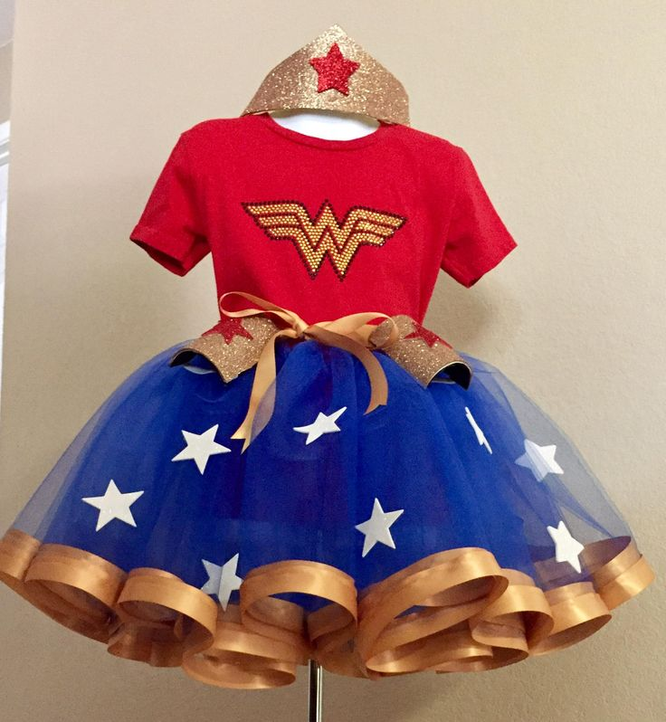 Your little super hero will love dressing up in this Wonder Woman inspired tutu outfit! This features an elastic waistband, satin edges and high quality tulle. Included are the shirt with a sparkly logo either as shown or with a sequin look depending on size, as well as the crown and wrist protect