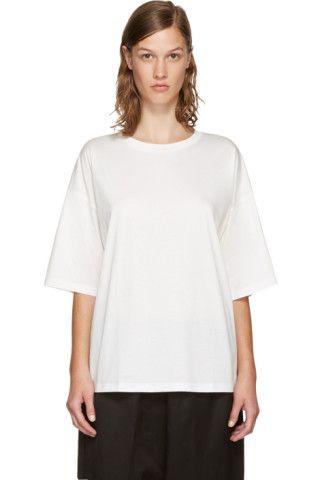 コットン ジャージの半袖 T シャツ。カラーはホワイト。クルーネックの襟はリブ編み。後部ウエストにシルクのセルフタイ式ストラップ。背面はクロップド ヘム。同系色ステッチ。