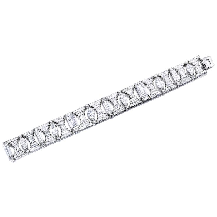 Diamond Bracelet, Cartier, Paris Of architectural design, the articulated band highlighted by marquise-shaped, rectangular-shaped, emerald-cut and baguette diamonds, to the border embellished with French-cut and baguette diamond details, the diamonds together weighing approximately 38.00 carats, mounted in platinum and 18 karat white gold, circa 1930, length approximately 180mm, signed.