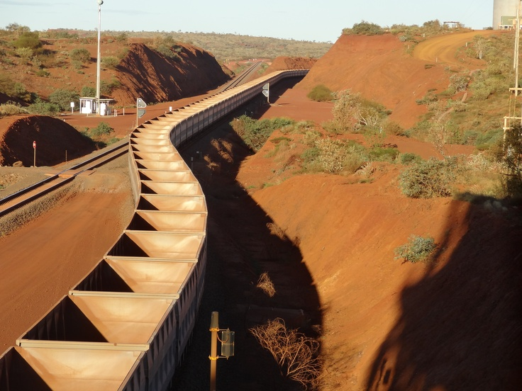 The longest train in the world is about to be loaded with iron ore. Then it heads from the Pilbara, towards Port Hedland where huge container ships wait to transport the precious minerals to Chinese steel mills