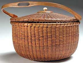 """Nantucket basket by A.D. Williams  with a round swing handle and a pagoda  cover has a handwritten paper label that  reads, """"Lightship Basket made by A.D...120  O...Nantucket."""" A brass plaque bears the  owner's name, """"Leila Carlisle""""; she purchased  the basket from A.D. Williams and  left her collection to Edgar and Katherine  Seeler in the 1920's."""