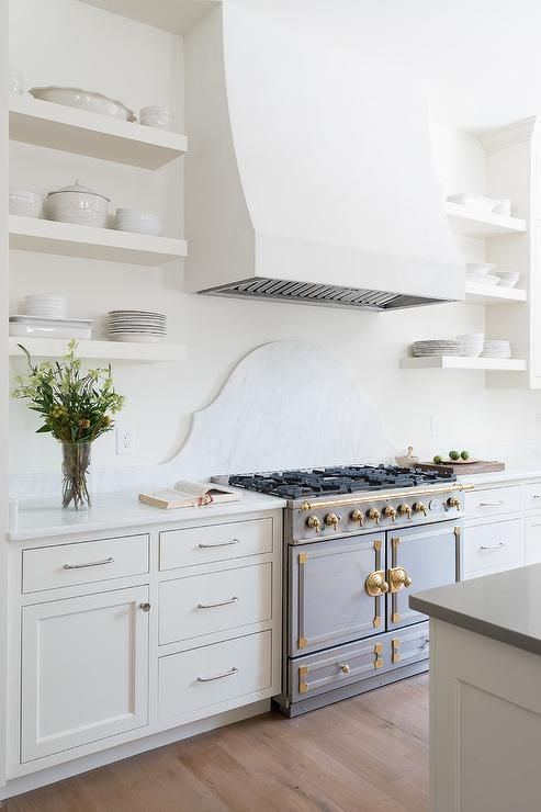 Kitchen with Solid White Open Shelves and Silver and Gold French Stove via Parkes and Lamb Interiors