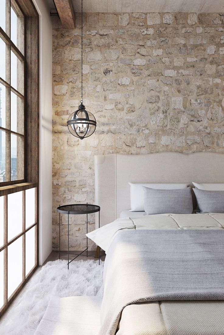 Stone and wood are classic textures that maintain their place as the most versatile interior decor elements. This natural bedroom embraces the rough stone with plenty of soft fabrics and abundant sunlight