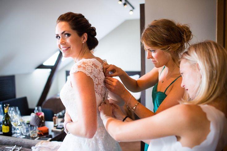 Bridesmaid helping bride zip up dress