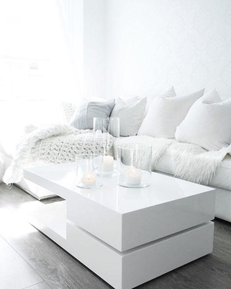 Pehmeät ja lämpimät tekstiilit tuovat kodikkuutta valkoisen hallitsemaan värimaailmaan olohuoneessa. Myös sohvapöydän persoonallinen muoto tuo oman isänsä kokonaisuuteen.