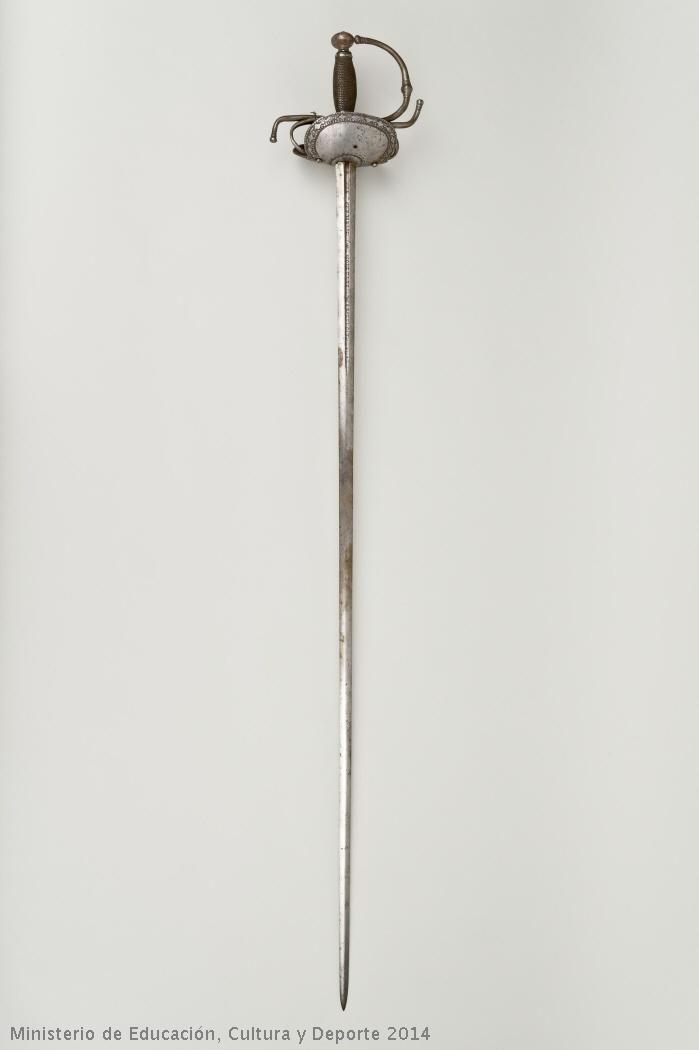"""Museo Arqueológico Nacional Espada ropera de acero tipo """"de concha"""", con guarnición simple de lazo. Los gavilanes de la cruz están curvados en sentidos opuestos. Posee hoja de dos mesas, acanalada en su primer tercio."""