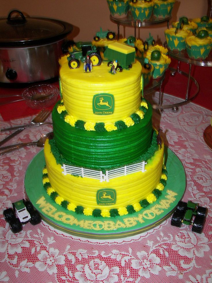 "John Deere Baby Shower Cake and Cupcakes - This cake was made for my brother-in law and sister-in law's baby shower celebrating the birth of their 3rd child finally a son. It is three tiers 10""-8"" and 6"". It was iced in all buttercream icing in John Deere colors Green and Yellow. The topper used is toy John Deere tractor pulling a wagon. The middle tier has a plastic fence with plastic horses. I piped grass with buttercream icing and a shell border for bottom and top tier. I used John Deere…"