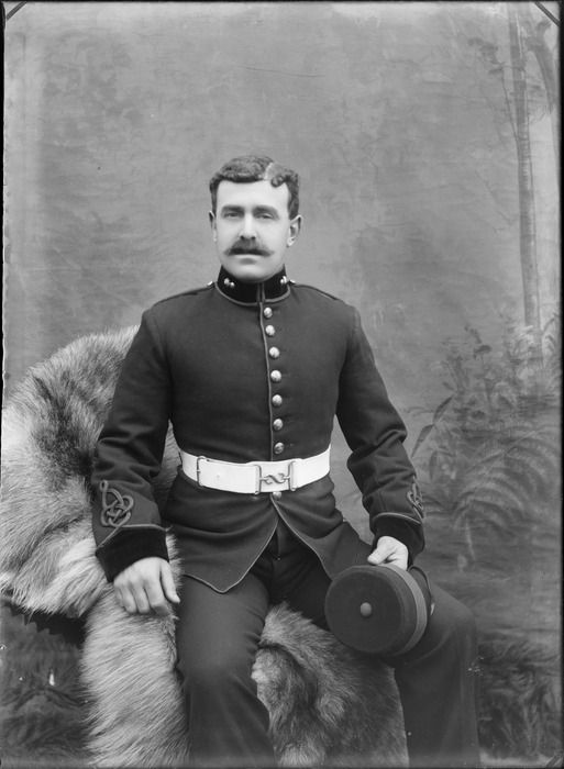 Outdoors in front of false backdrop, portrait of an unidentified soldier in dress uniform, with moustache, collar badges, sleeve insignia, sitting holding a domed cap, probably Christchurch region