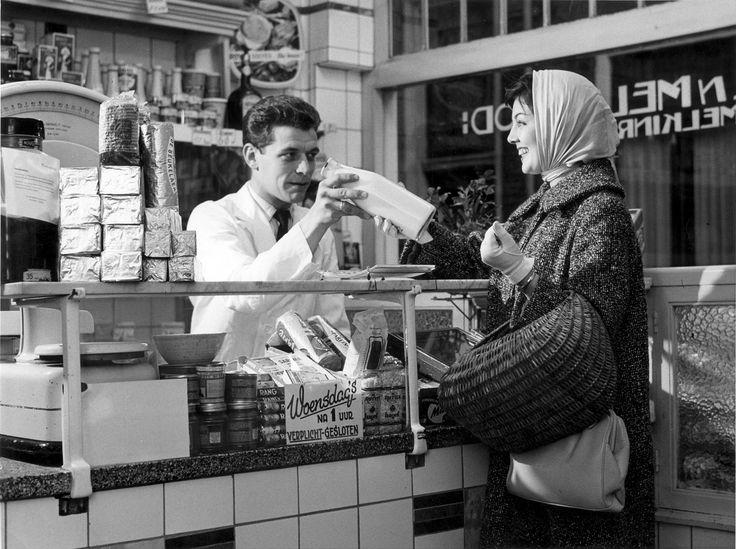 De kruidenier overhandigt een fles melk aan een mevrouw met een hoofddoek en een boodschappenmand, 1958.