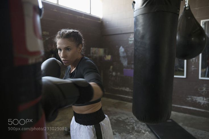 Serious tough female boxer boxing at punching bag in gritty gym by HeroImages