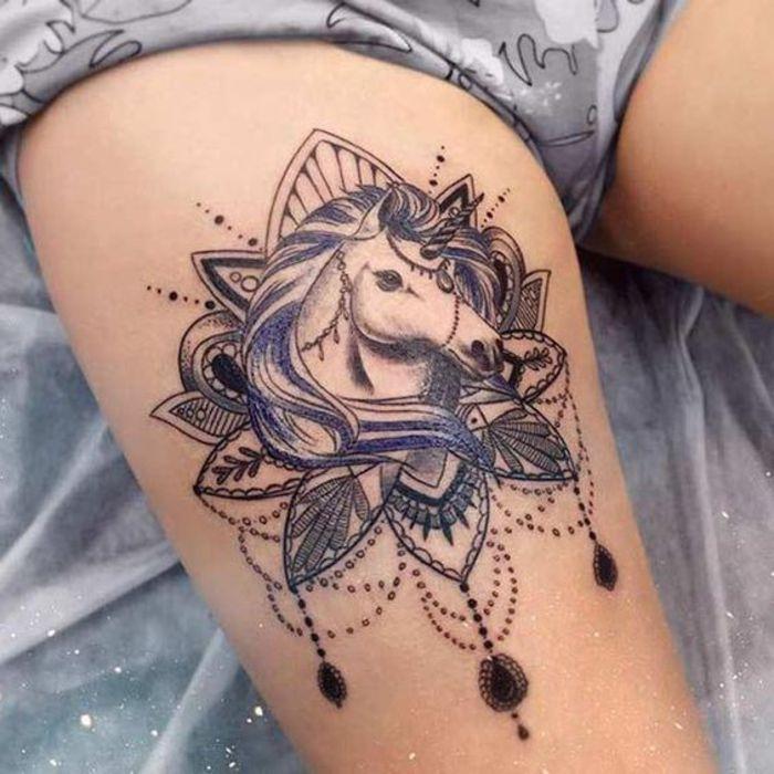 bein tattoo, einhorn, lila und schwarz,weibliche tattoo motive, tattoo am oberschenkel