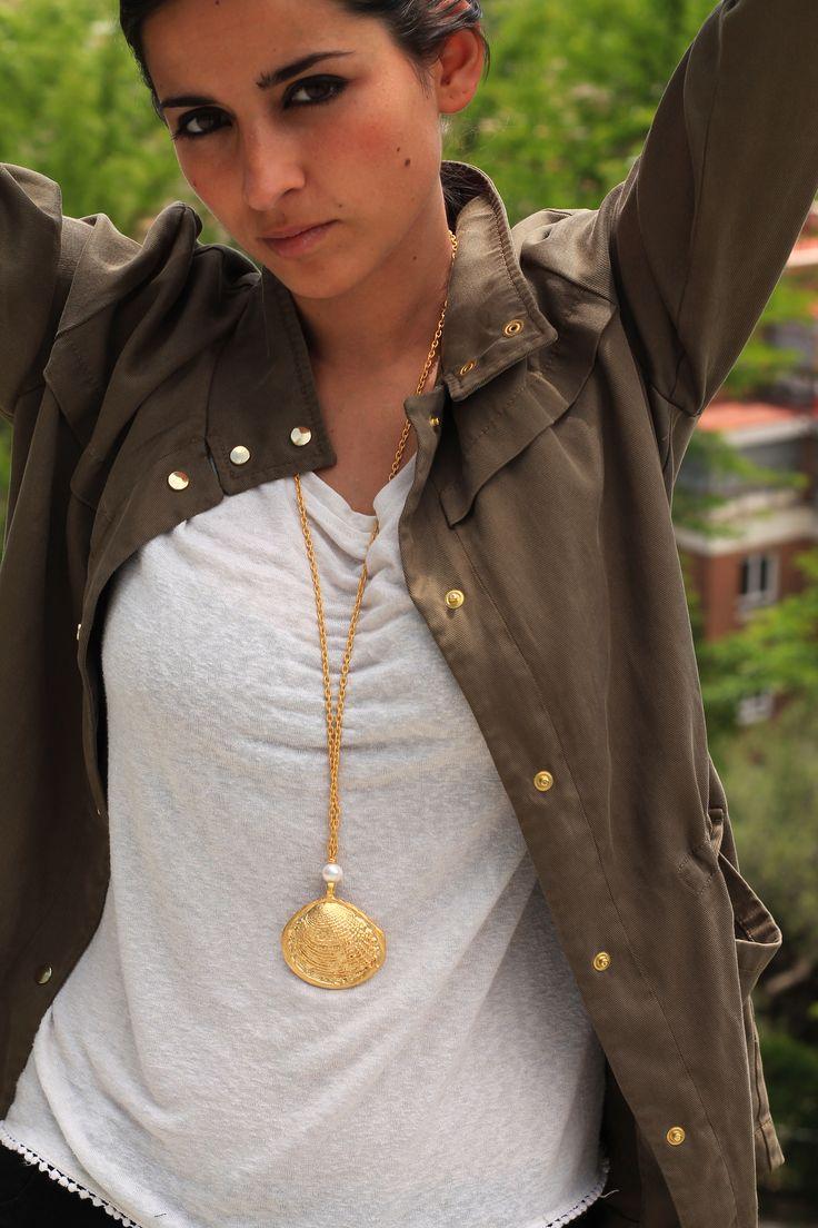 Precioso colgante en forma de concha bañado en oro de 18k con acabado mate, acompañado de perla de río y cadena bañada en oro con acabado mate.