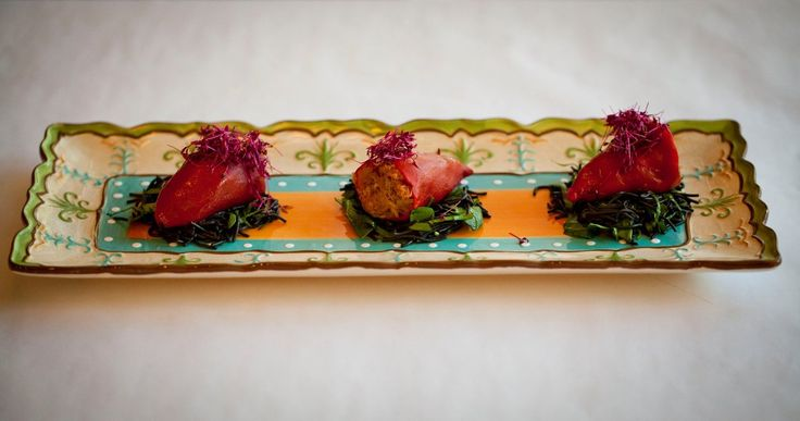Piments Pequillo farcis aux crabes et crevettes sur un lit de pâte noir.