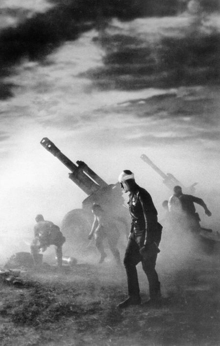 A Wounded Russian Soldier drifts past a 152mm Howitzer battery firing during the Belorussian Offensive Operation, 1944.