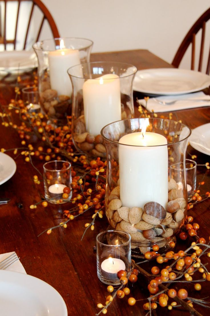 Fall table decor: I filled the bottom of three glass hurricanes with mixed nuts and added pillar candles. I then arranged five small votive holders within orange-berried branches and called it done! Not only was it simple and elegant, but you could actually see the people sitting across the table from you. :)