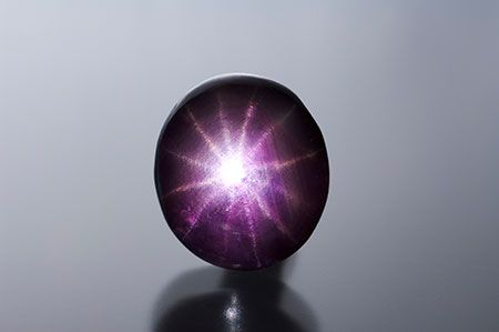"Purple 12-ray star sapphire, 8.13 ct, 11.78 x 10.50 x 6.28 mm. Unlike this one, such stones often are glass-filled. For a brief report on the phenomenon, see ""Twelve-rayed star sapphire of interest"" by Garry DuToit, GIA Laboratory, Bangkok."