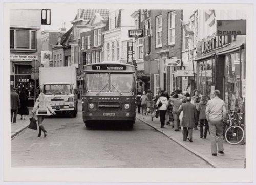 Stadsbus naar Schothorst die door de Langestraat rijdt, langs een geparkeerde vrachtauto. Rechts o.a. de winkel van Albert Heyn.