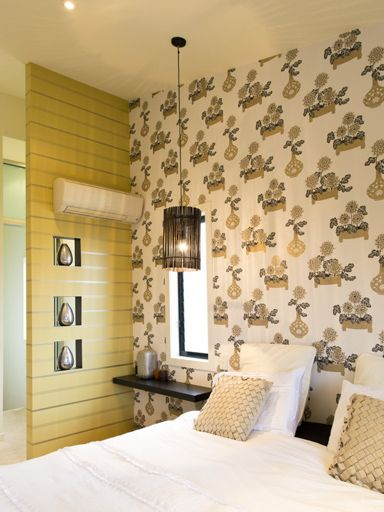 Using contrasting wallpaper patterns creates a juxtaposition that enlivens and enhances each paper as well as the other strong elements of the room like the light fittings and niches.