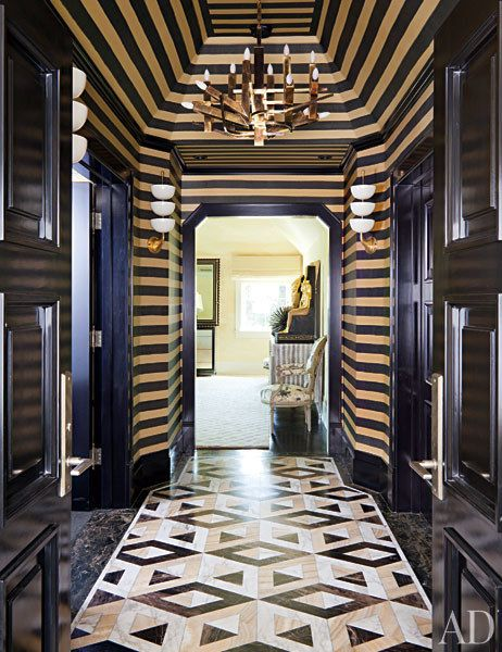 The master suite's striped vestibule is accented by an Italian modernist chandelier and vintage Stilnovo sconces.
