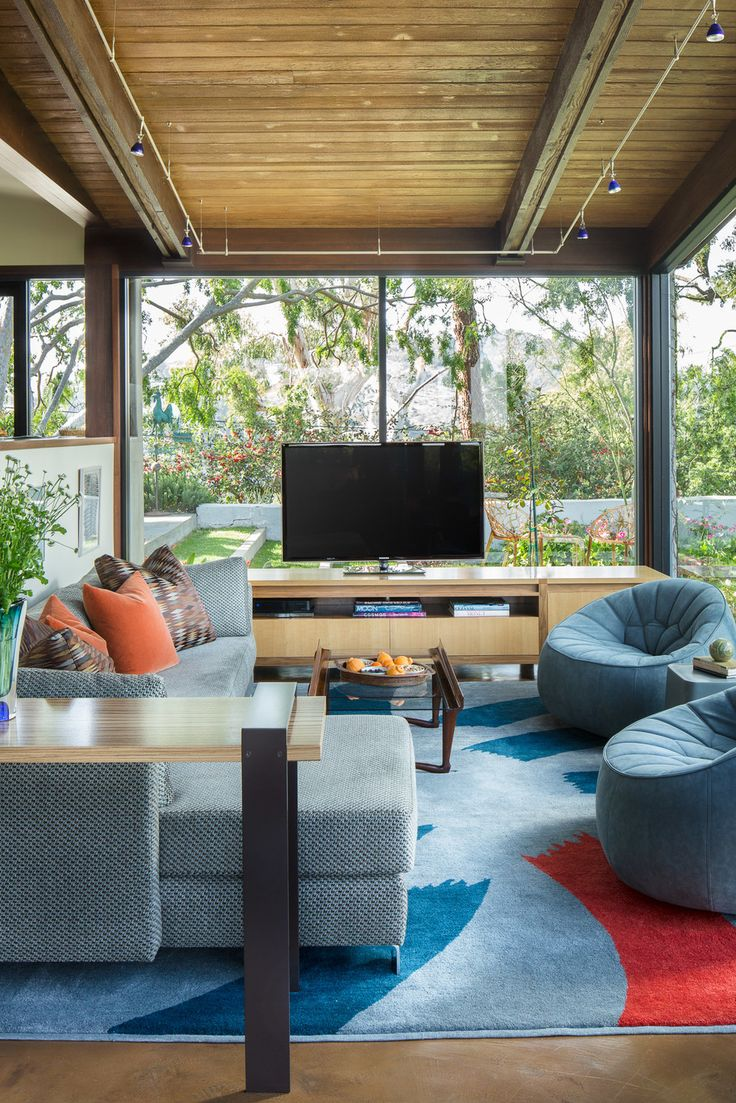 This fun contemporary living room features a neutral blue-toned sectional, lounge chairs reminiscent of bean bag chairs, a modern abstract rug, wall to wall windows, and a flat screen TV on a midcentury stand.