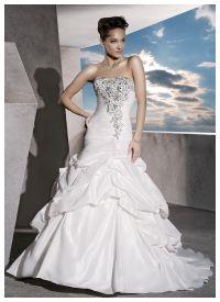 Эффектное свадебное платье прилегающего силуэта «fit'n'flare» из «крэш»-тафты. Задрапированный лиф с заниженной линией талии, сзади на шнуровке, спереди - богато украшен вышивкой бисером, стеклярусом, кристаллами, жемчужинами.  Защипы и подхваты формируют спереди эффект приподнятой верхней юбки, а сзади создают небольшой турнюр и ярусы-баллоны, раскрывающиеся в аккуратный шлейф
