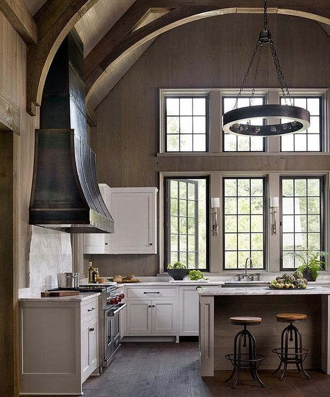 Cathedral Ceiling Kitchen. Kitchen with cathedral ceiling. Three steel swing-out windows hang over a stainless steel apron sink and Ruhlmann Single Sconces. #Kitchen #CathedralCeiling #KitchenCathedralCeiling Dungan Nequette.