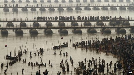 Hindu devotees take a dip at Sangam, the confluence of the Rivers Ganges, Yamuna and mythical Saraswati as others cross a make shift bridge, on one of the most auspicious day Makar Sankranti, the first day of the Maha Kumbh Mela, in Allahabad, India, Monday, Jan. 14, 2013. 80-100 million people are expected to take part.