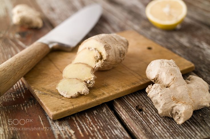 Pic: Sliced ginger and knife on wood cutting board rustic setting