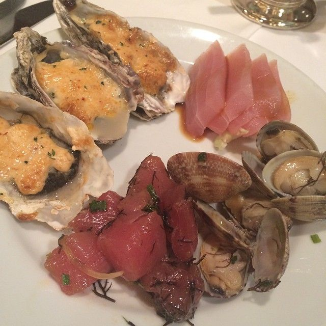 Seafood buffet with sashimi poke, clam poke, baked cheese oysters, tuna sashimi and king crab legs