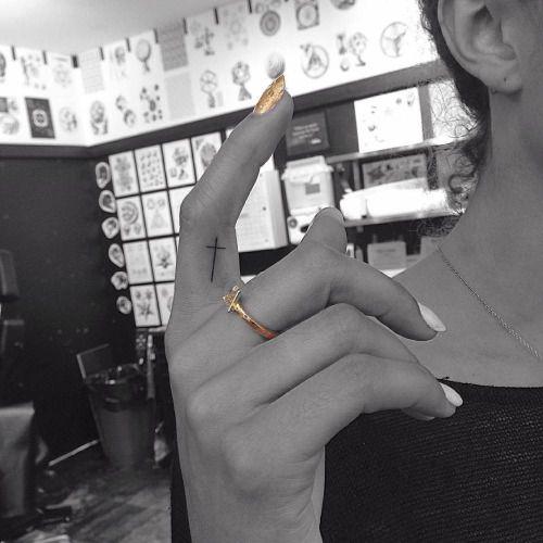 Minimalist cross on the right index finger. Tattoo artist: Jon...