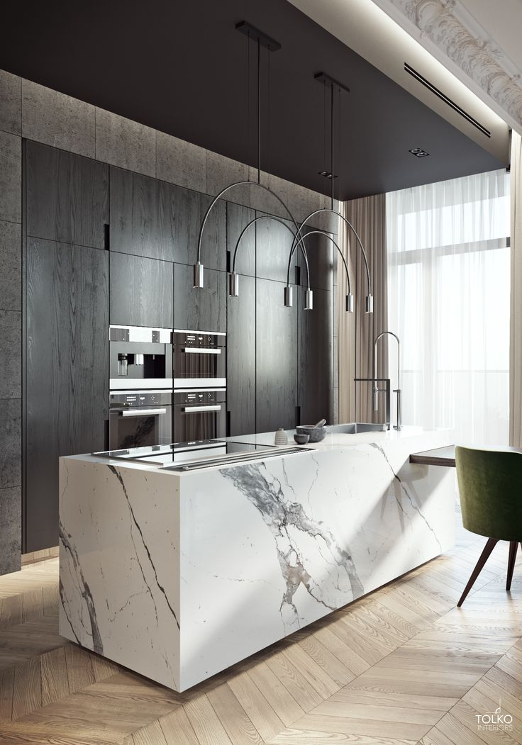 Big block white marble kitchen island with dark wood back drop cabinetry and herringbone light wood or tile floor. Love the extension table from the island. Very modern, luxorious and minimalistic