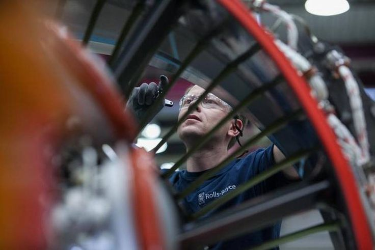 An employee inspects the turbofan blades of a Rolls-Royce V2500 aircraft engine, which power the Airbus 320 family of passenger aircraft, on the final assembly line inside Rolls-Royce Holdings Plc's aerospace unit factory in Dahlewitz, Germany.