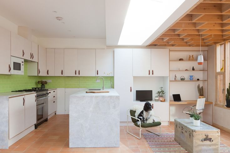 A slot roof light over the kitchen and a glazed roof to the side extension flood the new and existing spaces with natural light. The external walls of the extension are in a painted, textured render to tie the extension into the existing house. Internally earthy tones are used. Terracotta floor tiles.