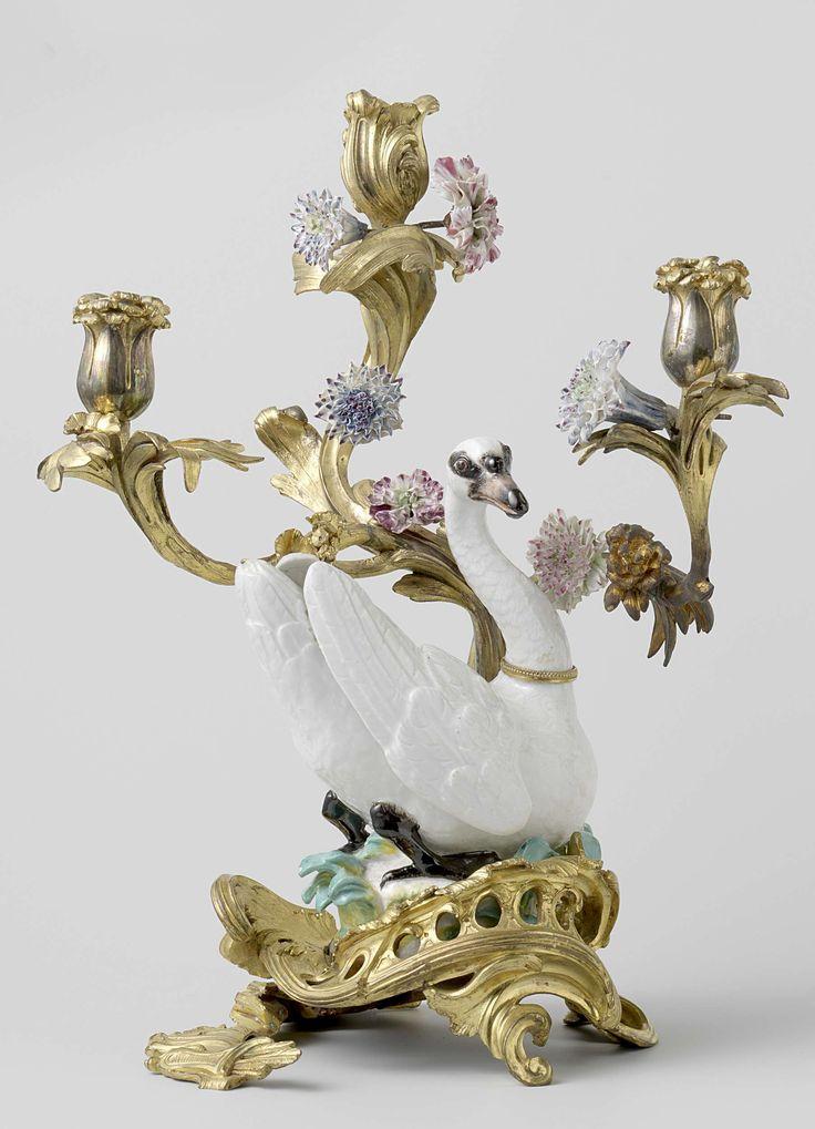 Anonymous | Zwaan van veelkleurig beschilderd porselein, in montuur van brons, Anonymous, Meissener Porzellan Manufaktur, c. 1748 | Zwaan van veelkleurig beschilderd porselein, op voetstuk met plastische bladversiering in blauwgroen, groen en geel. De zwaan heeft om de hals een ring van verguld brons. De zwaan is geplaatst in een verguld bronzen montuur in rococo-stijl, in de vorm van een drie-armige kandelaber, waaraan bloemen van porselein in blauw, roze, groen en violet zijn bevestigd. De…