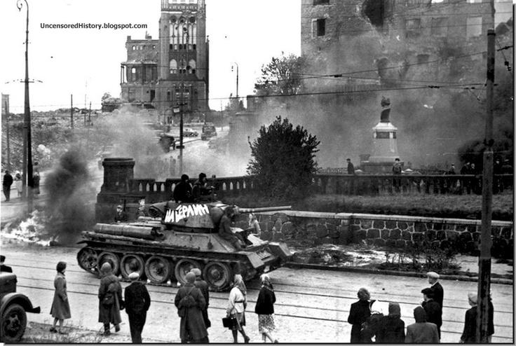 German people watch helplessly as a Red Army tank trundles on a street in Konigsberg in 1945