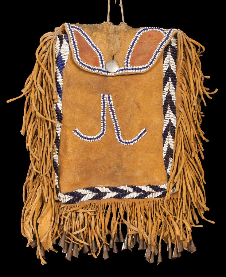 "Apache Beaded Bag Early Apache, heavily fringed flap bag with white and blue beads in classic Apache design, and tin cones along the bottom. Yellow and red pigments with Gan Dancer drawing on the back. Coin silver button holds the flap. 9"" x 12"", circa 1870s."