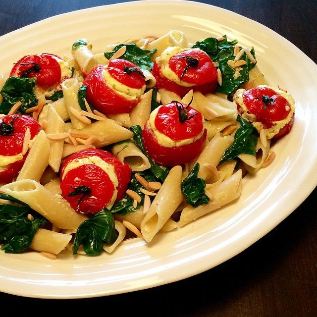 #MeatlessMonday  Oven-roasted stuffed tomatoes over pennoni with wilted spinach and toasted almonds. The goat cheese, basil & garlic filling perfectly coats the pasta in creamy deliciousness! #delicious #fresh #healthyfood #flavour @zimmysnook