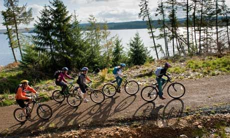 Ten top forests for cycling..... Family cycling along the Lakeside Way, Kielder Water & Forest Park, Northumberland, England.