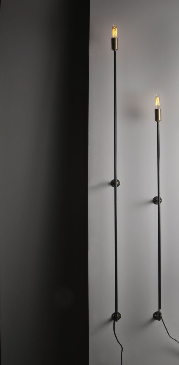 """Low profile, big visual impact. The Skinny Sconce does it's job and stays  out of the way but not without a huge visual impact. 3/8"""" blackened steel  tube with brass and steel wall mounts. Accepts candelabra bulbs (Edison  style included) in a brushed brass cup. Cord has black inline switch for  powering on and off. Standard lengths from tip of bulb are 38"""" and 51"""".  Custom sizes available."""