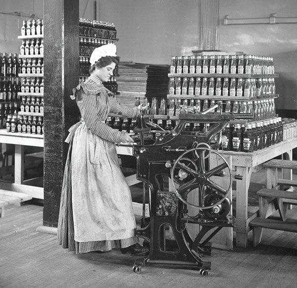Female worker bottling ketchup at the original Heinz factory circa 1897. Pittsburgh, PA.