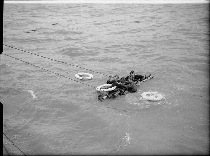 Landing craft gun survivors clinging to a raft as they are pulled towards their rescuers' craft (not in shot). A lifebelt has just hit the surface of the water next to them.