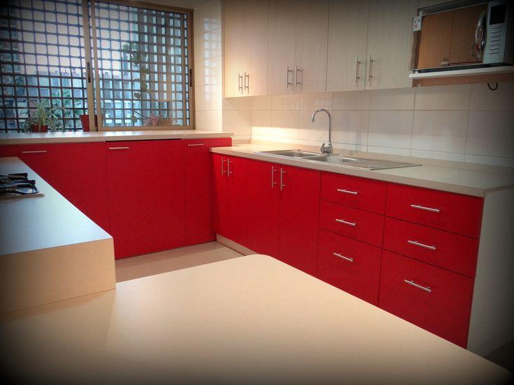 Cocina remodelada en dos tonos, con cubierta post formada, lavaplatos empotrado y espacio para secadora y lavadora oculto tras puertas.