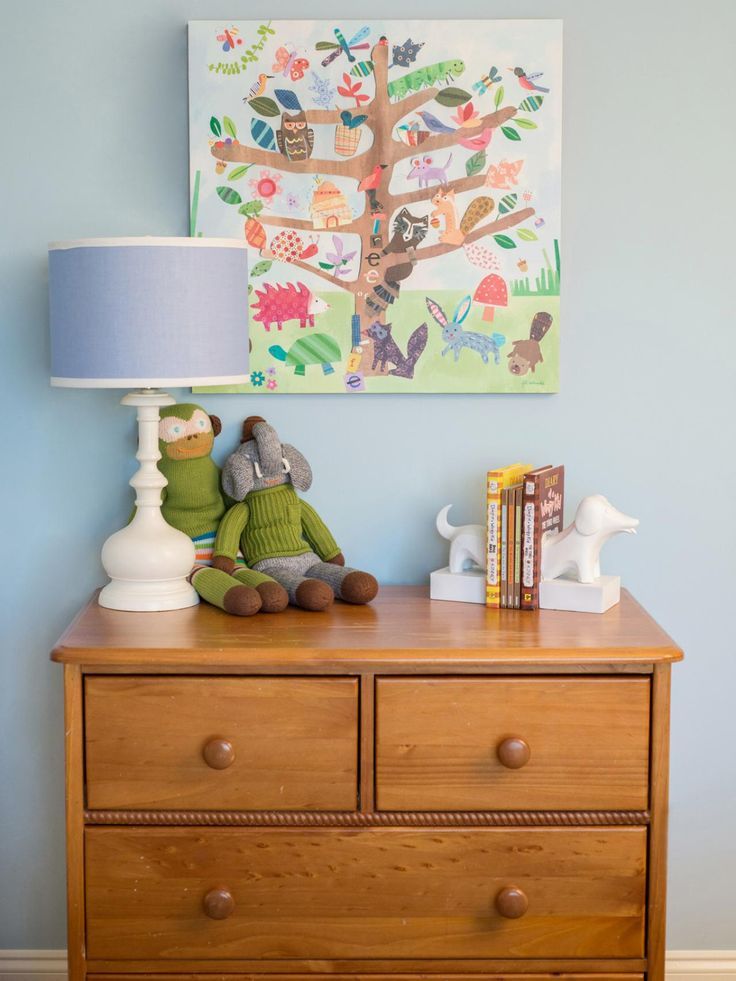 A classic cottage-style pine dresser serves as the resting place for playful dog bookends and stuffed toys in this transitional boy's bedroom. A colorful and whimsical painting featuring forest critters takes center stage above.