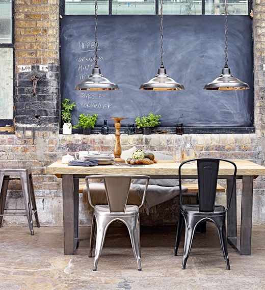 Chic industrial dining space with chalkboard wall and mixed Tolix chairs. Love that rustic wood + steel table. #kathykuohome
