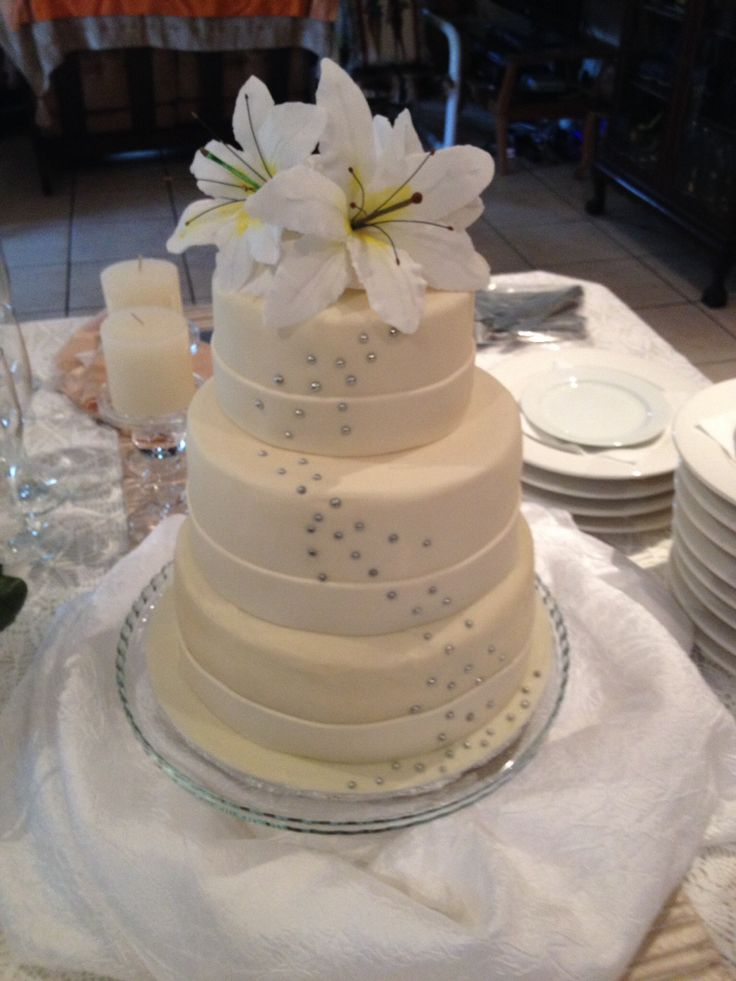 Three tier chocolate wedding cake covered with white chocolate ganache, with hand made gum paste lilies. By Chaos Cakes za   Like us on Facebook at https://www.facebook.com/chaoscakes1