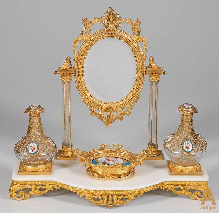 Элегантный туалетный гарнитур, состоящий из зеркала, флаконов для духов и вазона для хранения украшений, украшенные фарфоровыми вставками.