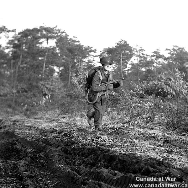 The Netherlands - Private W. Smith of The Highland Light Infantry of Canada training to operate a Lifebuoy flamethrower, Nijmegen, Netherlands, 14 December 1944.